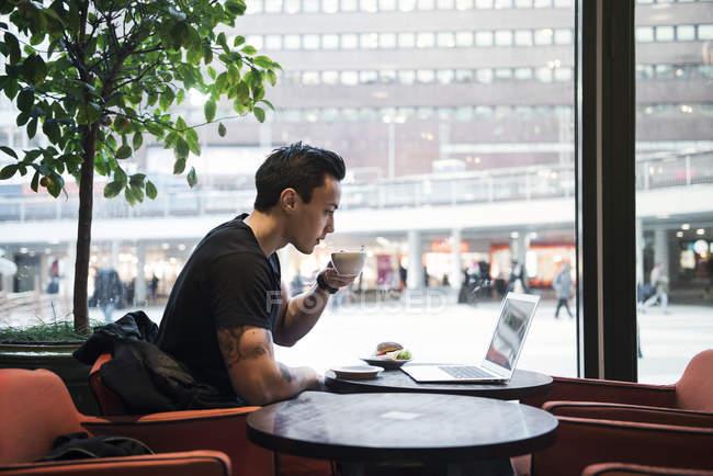 Uomo che utilizza il computer portatile in caffè, concentrarsi sul primo piano — Foto stock