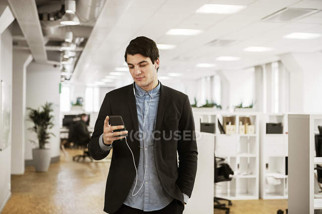 Young man using smart phone in office — Stock Photo
