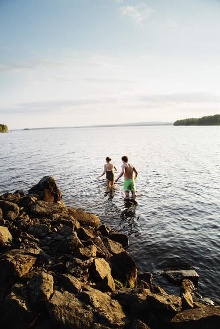 Mature woman and teenage boy in lake — Stock Photo
