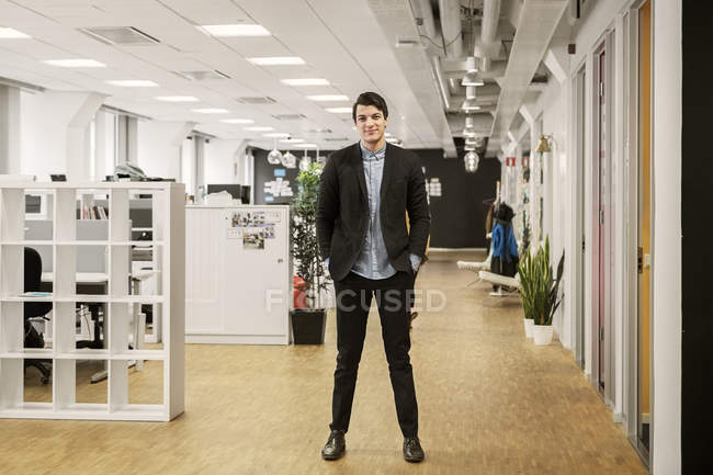 Young man standing in office, focus on foreground — Stock Photo