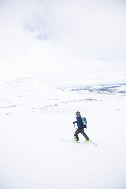 Homem atravessam país esquiando em belas montanhas cobertas de neve — Fotografia de Stock