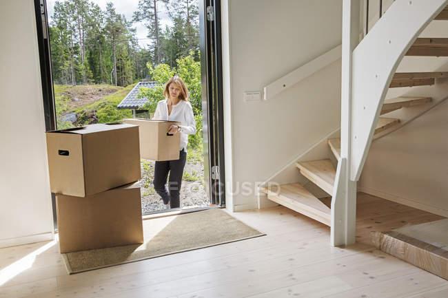 Mulher transportando caixa de papelão em casa — Fotografia de Stock