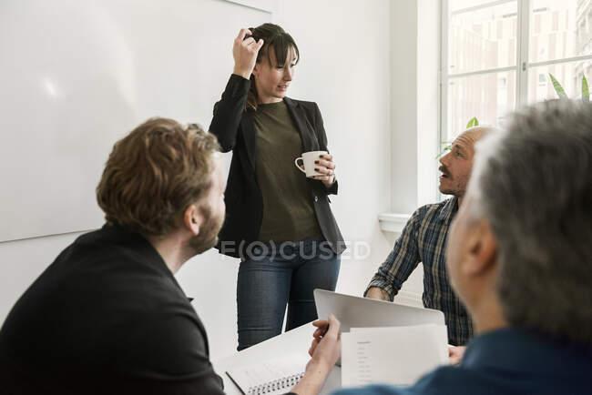 Les gens d'affaires se regardent et discutent du projet au cours de la réunion — Photo de stock