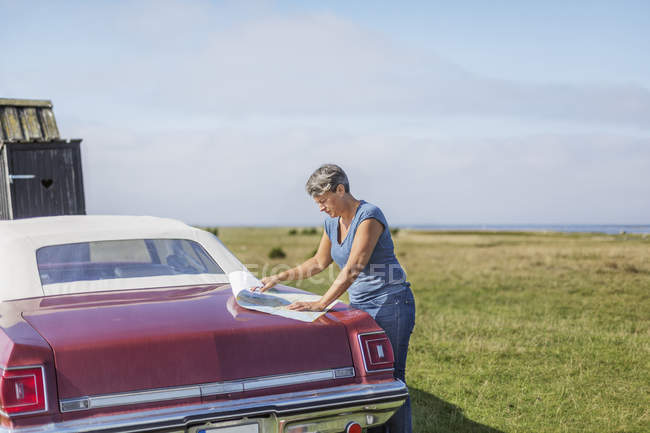 Mature woman traveling on vintage car, looking on map at field — Stock Photo