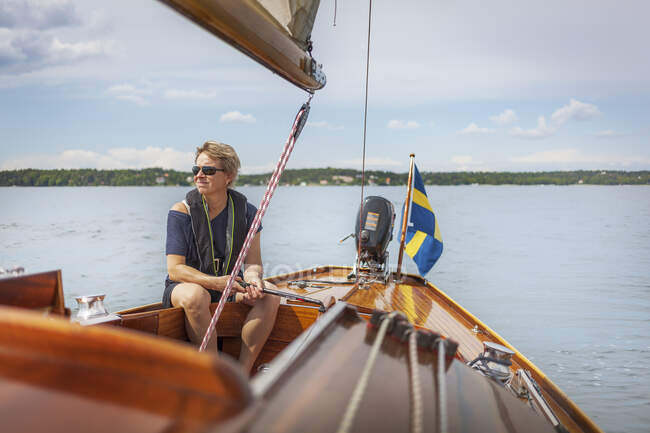Mid adult woman sailing on her yacht — Stock Photo