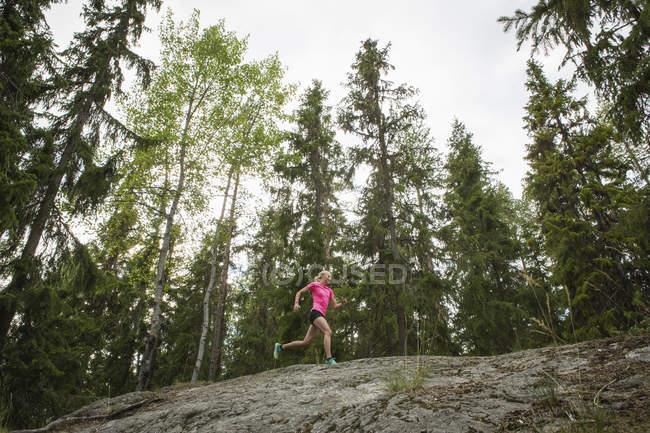 Femme courant dans la forêt, objectif sélectif — Photo de stock