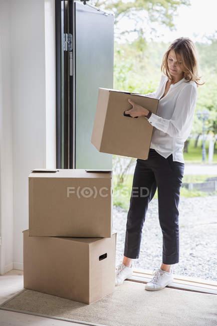 Cajas de cartón desembaladas femeninas en la nueva casa - foto de stock