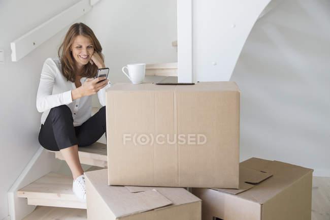 Mulher sentada nas escadas e usando smartphone — Fotografia de Stock