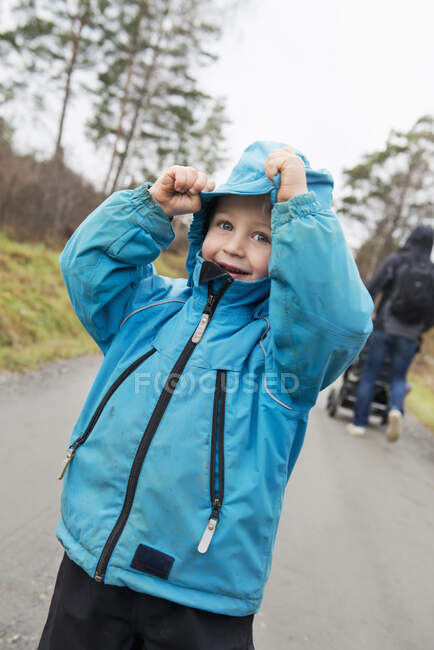 Cute happy boy wearing blue coat outdoors — Stock Photo