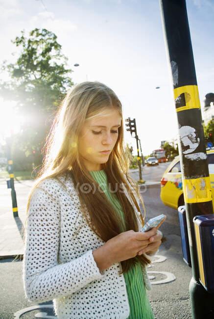 Девочка-подросток текстурирует через смартфон на улице — стоковое фото