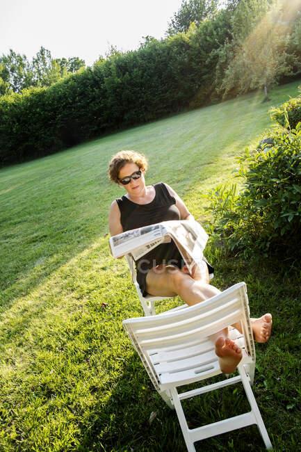 Femme assise sur une chaise et lisant un journal par temps ensoleillé — Photo de stock