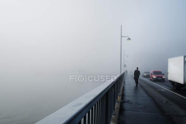 Hombre caminando por el puente el día de la niebla en Estocolmo - foto de stock