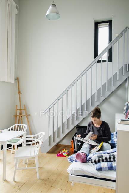 Зрелая женщина читает в квартире — стоковое фото