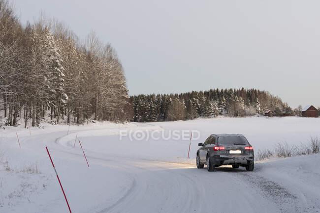 Auto guida su strada rurale innevata in inverno — Foto stock