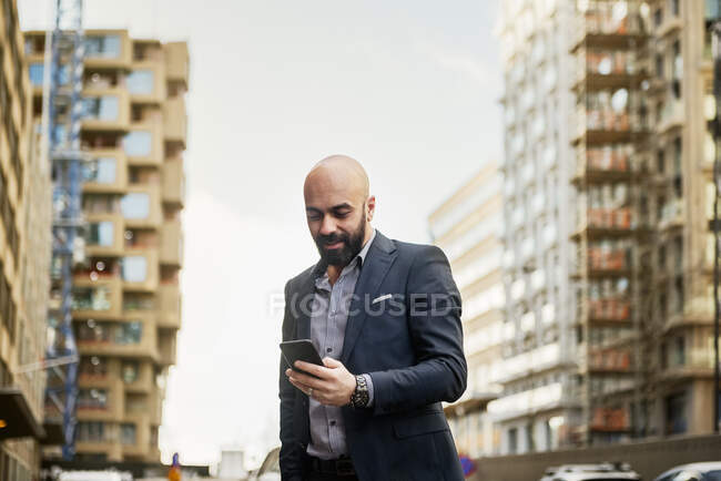 Low angle view of smiling bearded businessman using smartphone in city — Stock Photo