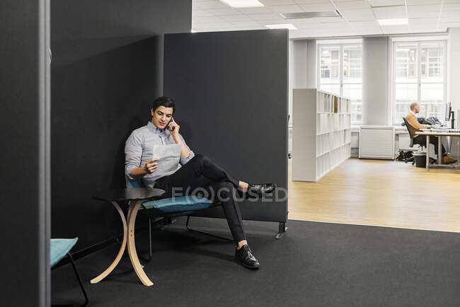 Молодий чоловік сидить і розмовляє по телефону в офісі. — стокове фото