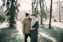 Stylish young couple embracing in sunny park — Stock Photo