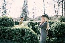 Junge Frau mit Dreadlocks mit Mann posiert in Hecke im park — Stockfoto