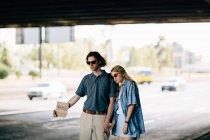 Молода пара в сонцезахисні окуляри автостопом з знак картону — стокове фото