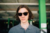 Jeune garçon dans des lunettes de soleil rétro regardant la caméra — Photo de stock