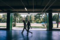 Silhouettes of couple walking at parking on background of sunlit street — Stock Photo