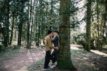 Young couple kissing by tall tree trunk at park\ — Photo de stock