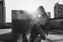 Young adult couple hugging on city street against sky, black and white — Stock Photo