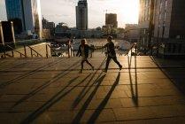 Vista panorámica de las siluetas de pareja de adultos jóvenes contra la luz del atardecer - foto de stock