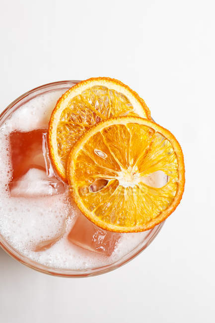 Refreshing drink decorated with orange slices over white — Stock Photo