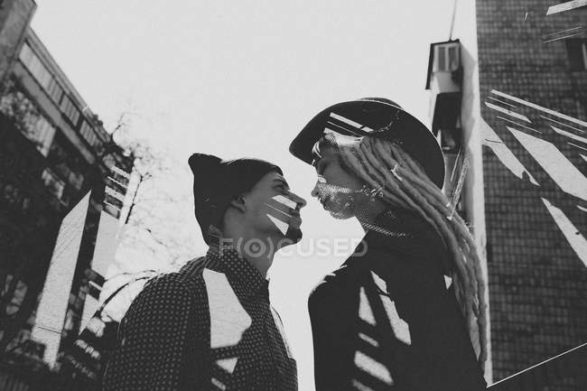 Young couple standing face to face in sunlight on street — Stock Photo
