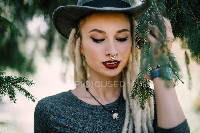 Portrait of stylish woman with dreadlocks under coniferous tree — Stock Photo
