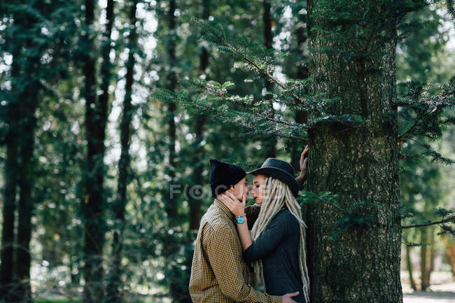 Stylish young couple leaning on tree trunk in woods — Stock Photo