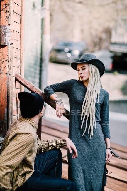 Frau mit Dreadlocks lehnt an Geländer und schaut auf Freund herab — Stockfoto