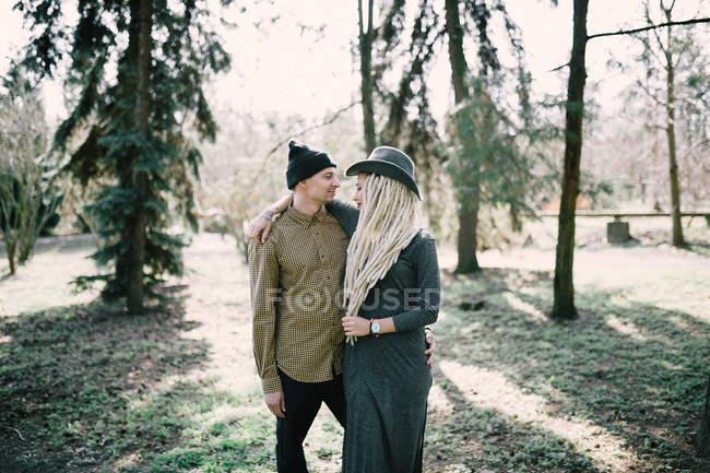 Стильная молодая пара, обнимающаяся в солнечном парке — стоковое фото
