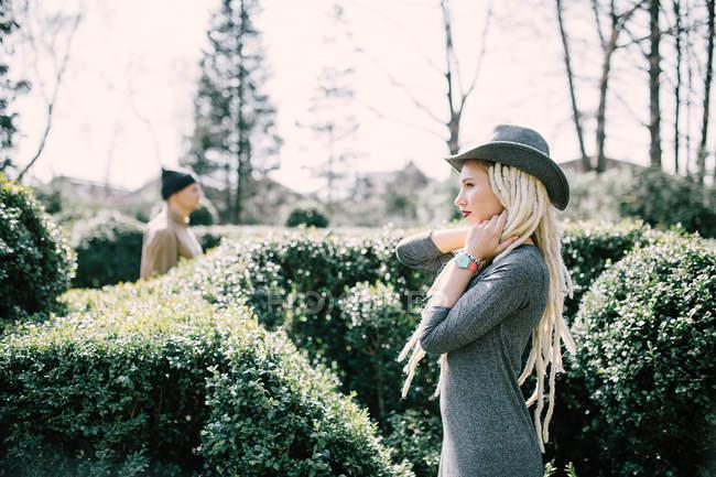 Молода жінка з дреди з людиною в хедж в парку себе — стокове фото