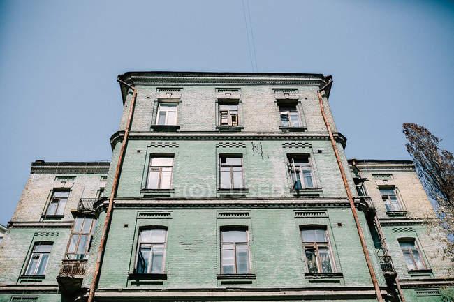 Vista exterior de la fachada del antiguo edificio verde sobre azul cielo - foto de stock