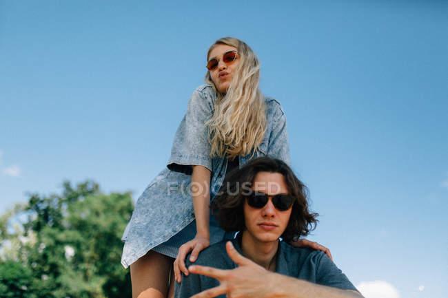 Giovani coppie che propongono alla macchina fotografica sopra il cielo chiaro — Foto stock