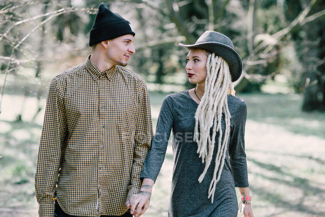 Young couple walking at nature and looking at each other — Stock Photo