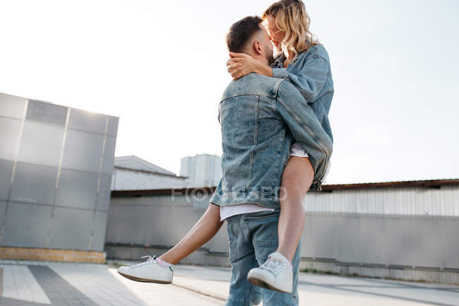 Young adult couple hugging on city street against sky — Stock Photo