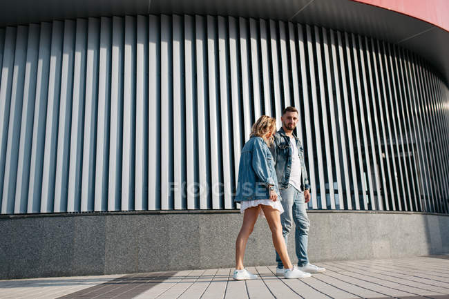 Young adult couple wearing casual clothing strolling outdoors — Stock Photo