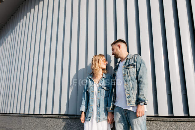 Young adult couple wearing casual clothing standing near wall — Stock Photo