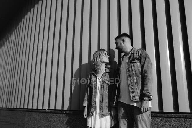 Young adult couple wearing casual clothing standing near wall, black and white — Stock Photo
