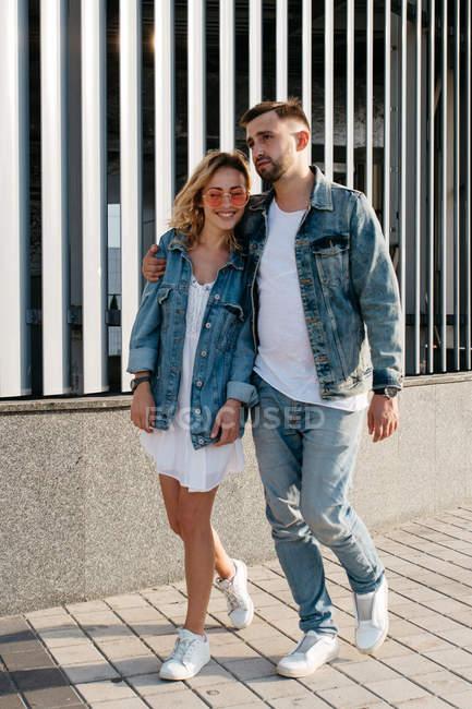 Jovem casal adulto vestindo roupas casuais passeando ao ar livre — Fotografia de Stock