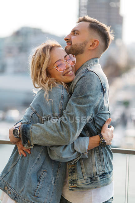 Scenic view of embracing young adult couple against modern cityscape — Stock Photo