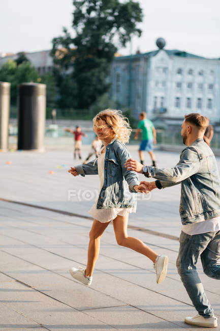 Young adult couple fooling around on city street — Stock Photo