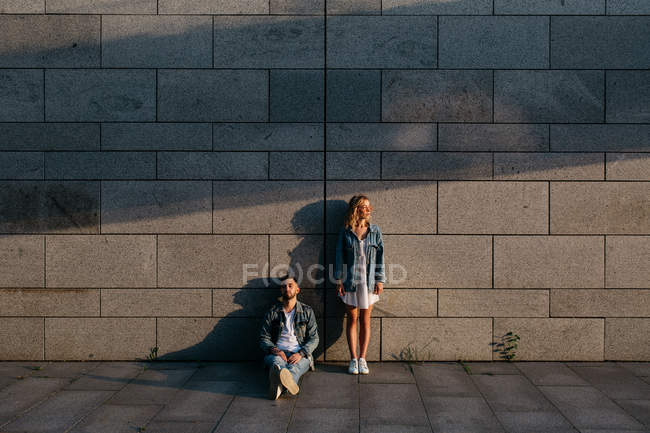 Young adult couple in casual clothing near gray wall — Stock Photo