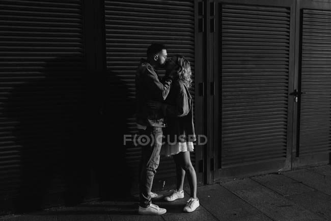 Vista laterale di baciare giovane coppia adulta vicino persiane di legno, in bianco e nero — Foto stock