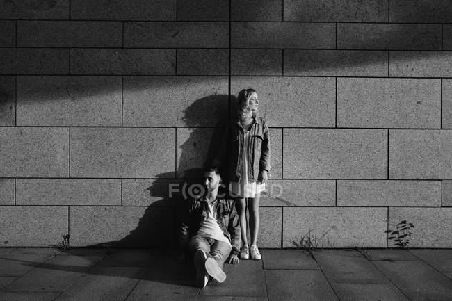 Jeune couple adulte dans des vêtements tout-aller près d'un mur gris, noir et blanc — Photo de stock