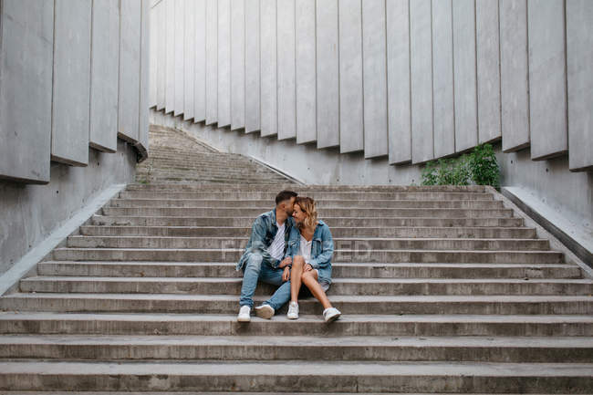 Young adult couple in casual clothing on concrete steps — Stock Photo