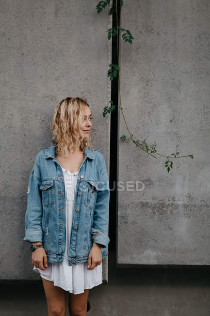 Young adult woman in casual clothing against gray wall — Stock Photo